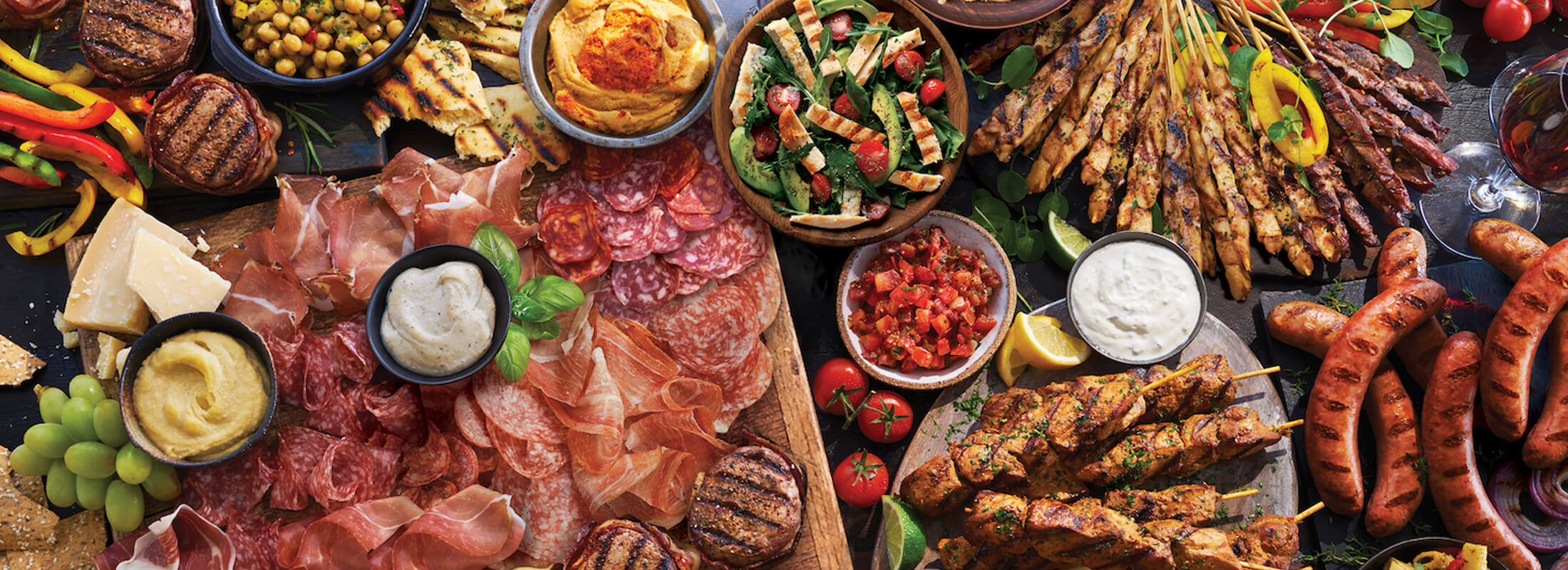 Marcangelo products - skewers, sausages, porchetta, strips, and meat products on table